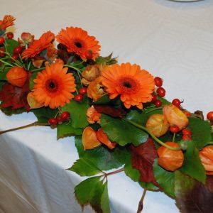 Syksyn värejä morsiuspöydän kukka-asetelmassa