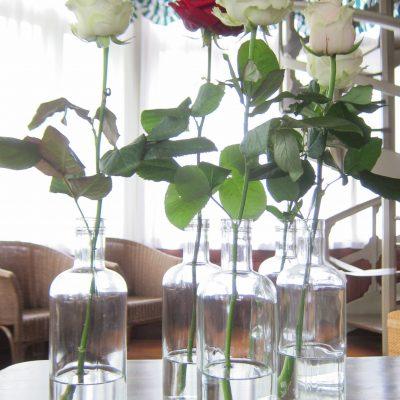 Yksittäinen ruusu pullossa pöyäkoristeena