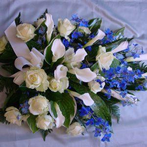 Täyteläinen surulaite valkoisista ruusuista ja kalloista sekä sinisistä ritarinkannuksista
