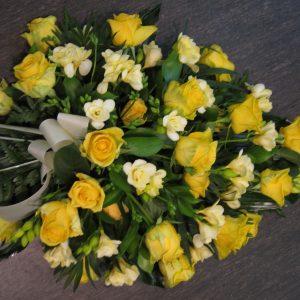 Keltainen surulaite ruusuista ja neilikoista