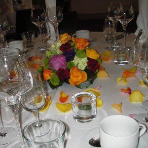 Monivärinen pöytäkoriste ja ruusun terälehtiä