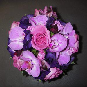 Lilansävyinen hääkimppu ruusuista, eustomista ja orkideoista