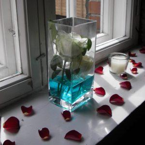 Ruusut lasisa ja terälehdet ikkunalaudalla