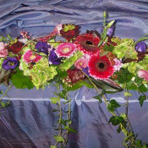 Morsiuspöydän voimakkaanvärinen kukka-asetelma